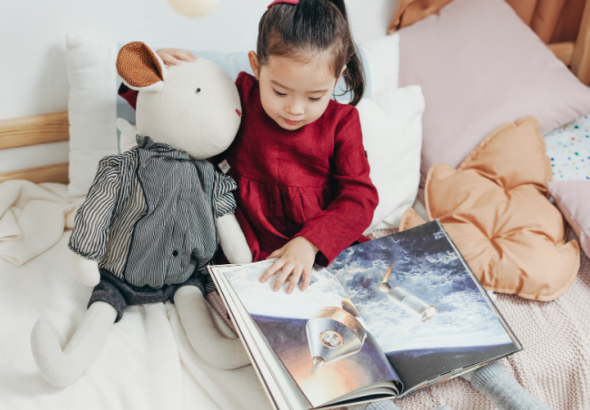A young girl reading book and hugging her toy.